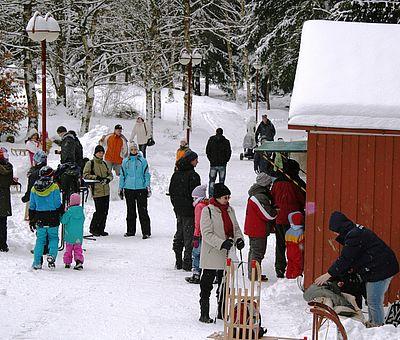 Menschen vor einer Hütte im winterlichen Kurpark