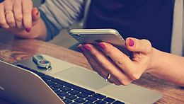 Eine Frau sitzt vor einem Laptop mit einem Smartphone in der Hand